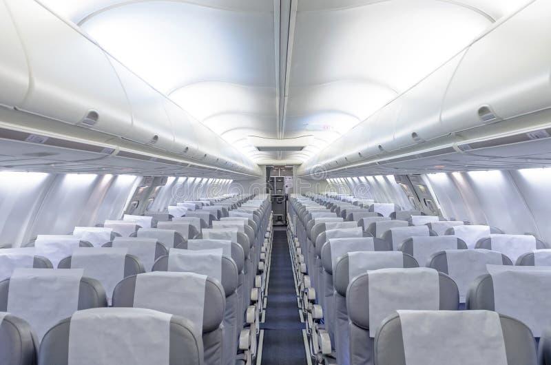 Commerciële vliegtuigencabine met rijen van zetels onderaan de doorgang royalty-vrije stock fotografie