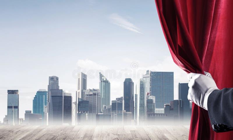 Commerci?le stad in grijze mist achter rode gordijn en handholding het royalty-vrije stock afbeelding