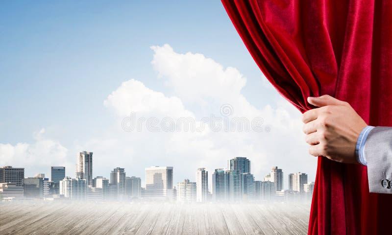 Commerci?le stad in grijze mist achter rode gordijn en handholding het stock fotografie