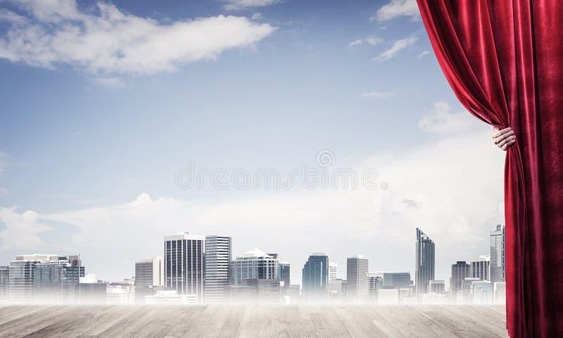 Commerci?le stad in grijze mist achter rode gordijn en handholding het royalty-vrije stock foto