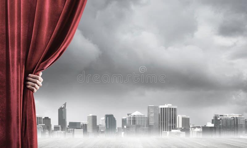 Commerci?le stad in grijze mist achter rode gordijn en handholding het stock foto