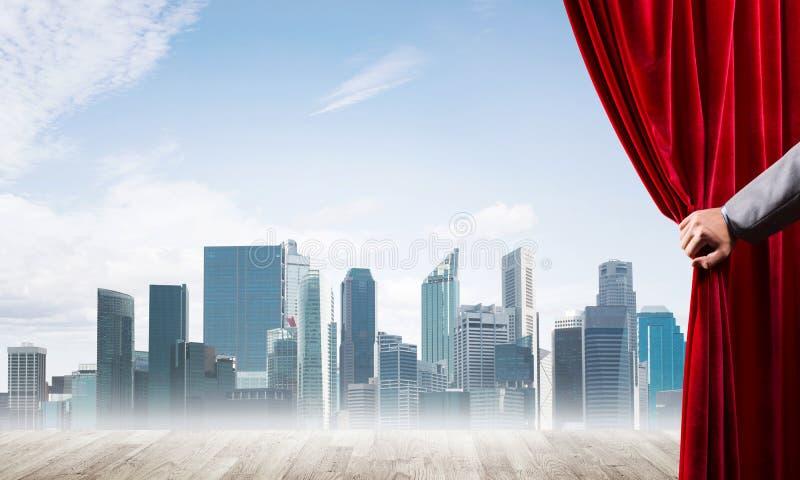 Commerci?le stad in grijze mist achter rode gordijn en handholding het stock afbeeldingen