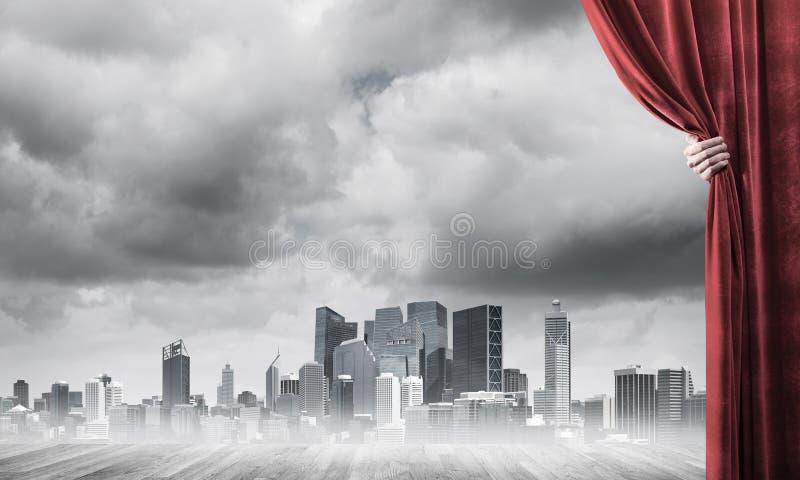 Commerci?le stad in grijze mist achter rode gordijn en handholding het royalty-vrije stock fotografie