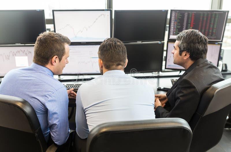 Commerci?le teambrainstorming terwijl het controleren van gegevens bij de computerschermen royalty-vrije stock fotografie