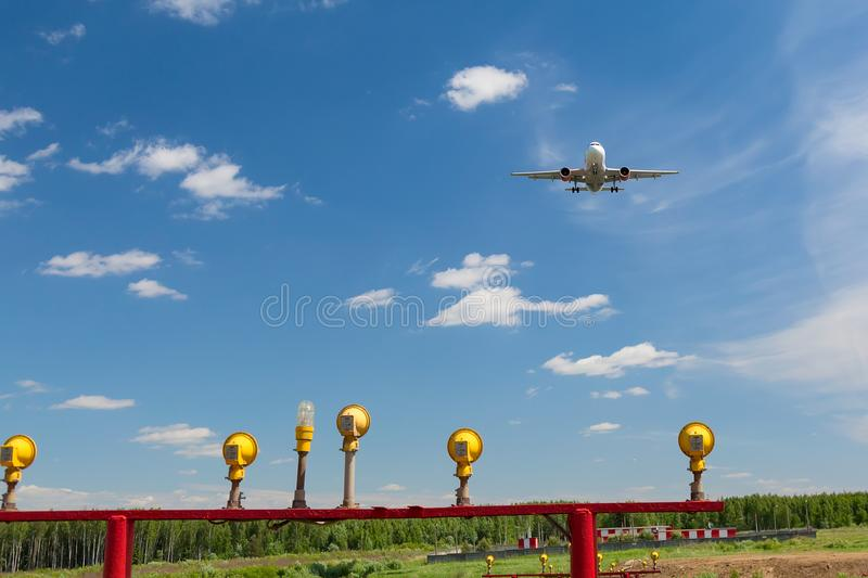 Commercial aircraft flying near clouds and landing with blue sky and landing lights. Travel or business trip concept image. Commercial aircraft flying near stock images