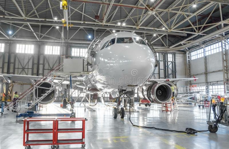 Commercial aircraft jet on maintenance of engine and fuselage check repair in airport hangar.  stock images