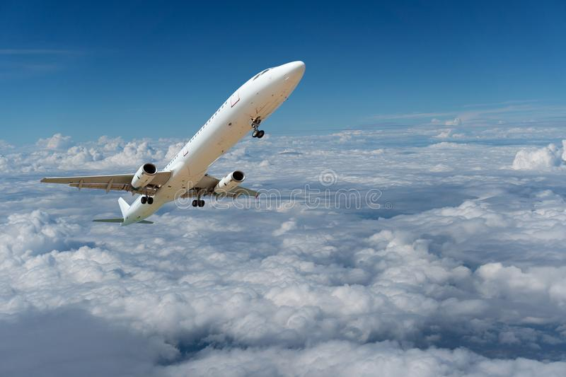 Commercial airplane flying above clouds and clear blue sky over stock photography