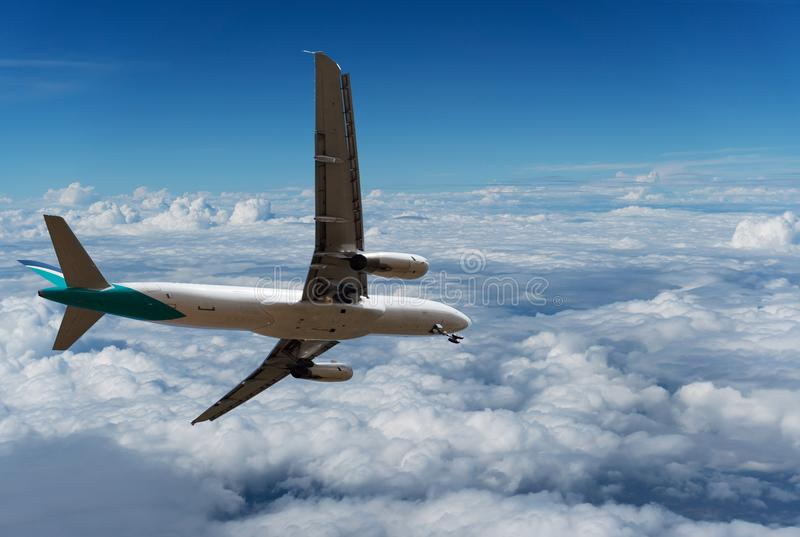 Commercial airplane flying above clouds and clear blue sky over stock photos