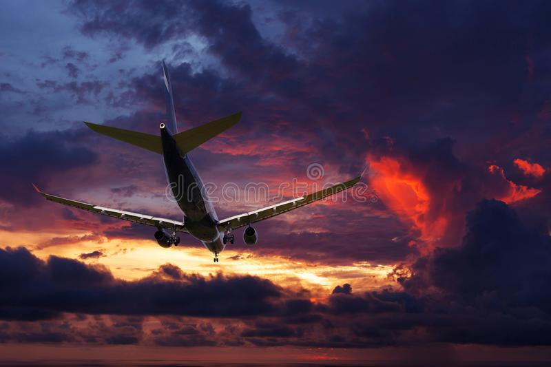 Commercial airplane flying above clouds with dramatic sunset or stock photos