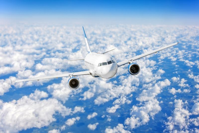Commercial airplane flying over bright blue sky and white clouds. Commercial airplane flying over bright blue sky and white clouds stock image