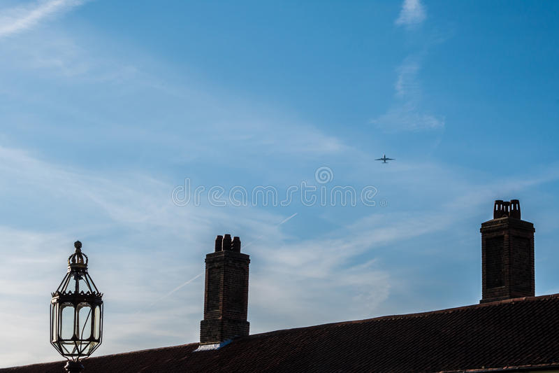 Commercial airplane flying over Tudor period rooftop with chimneys royalty free stock images