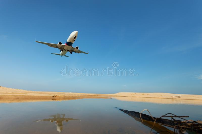 Commercial airplane landing above sea and clear blue sky over be royalty free stock image