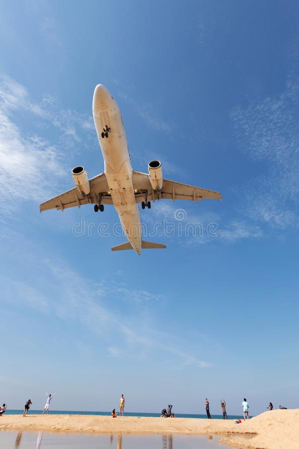 Commercial airplane landing above sea and clear blue sky over be royalty free stock photography
