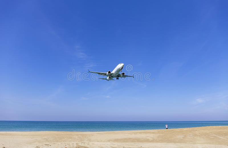 Commercial airplane landing above sea and clear blue sky over beautiful scenery nature background location at mai khao beach royalty free stock photo