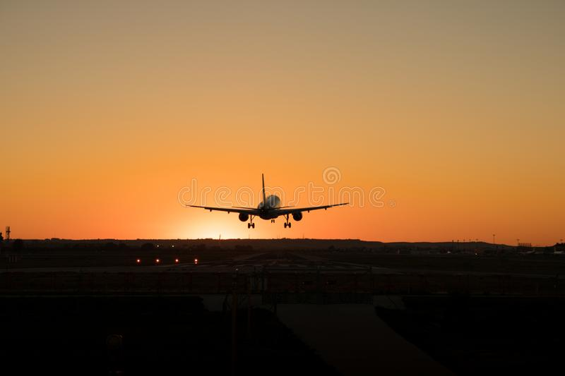 Commercial airplane is landing on the airport runway during sunset royalty free stock photography