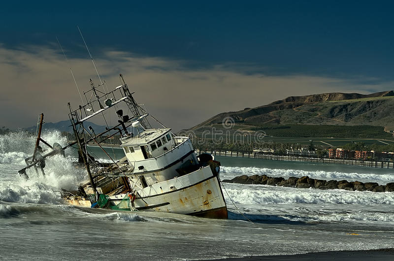 Commercial Boat. The day after a Pacific storm crashed onto Ventura beaches a commercial fishing boat ran aground in the remaining high tides and heavy swells stock image