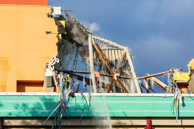 Commercial building collapsing during demolition job with a cloud of dust and large chunks of debris falling down.  royalty free stock image