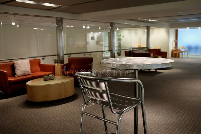 Commercial Business Lobby Waiting Area. A modern commercial business waiting area with metal table, chairs, couch, and glass wall stock photo