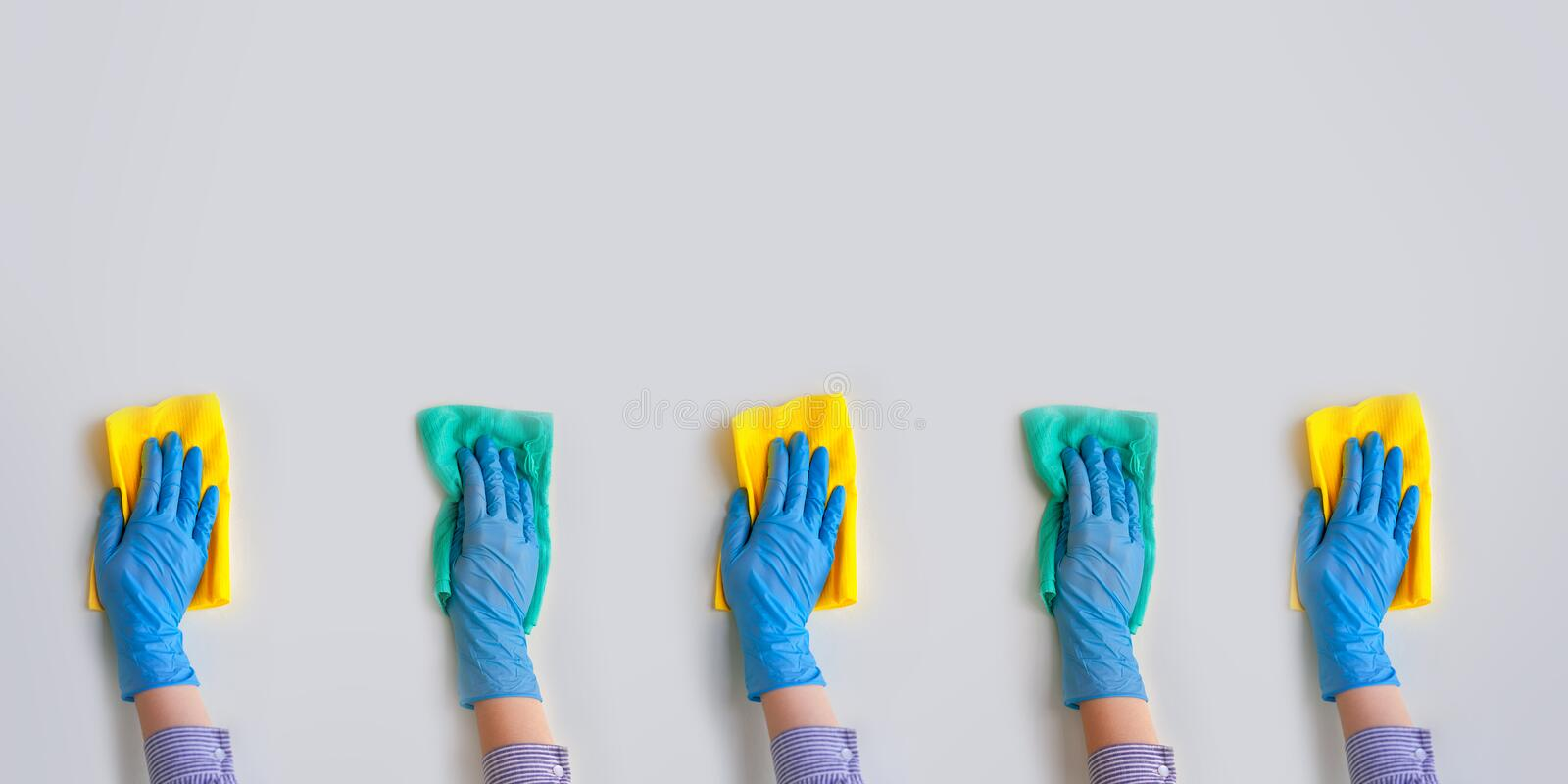 Commercial cleaning company. Employee hands in blue rubber protective glove. General or regular cleanup stock image