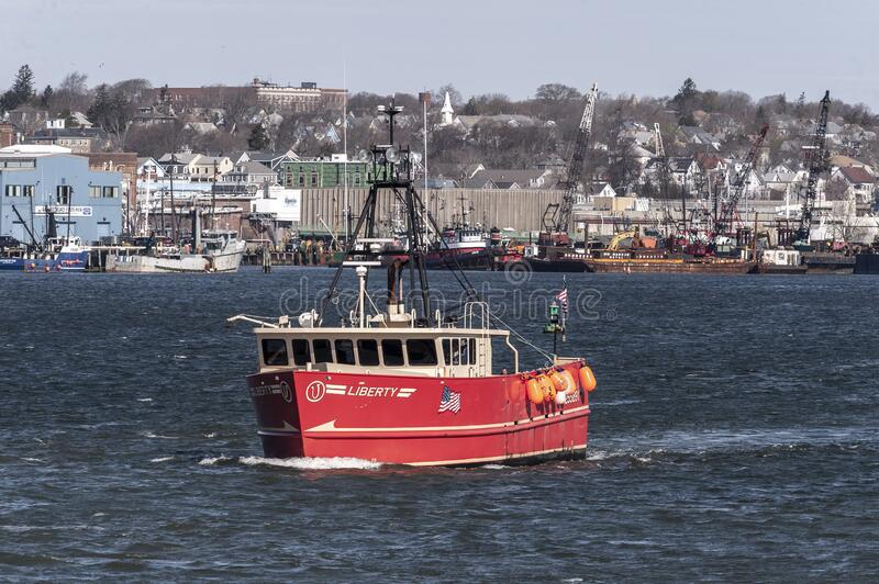 Commercial fishing boat Liberty outbound from New Bedford. New Bedford, Massachusetts, USA - April 14, 2020: Colorful commercial fishing boat Liberty leaving stock photography