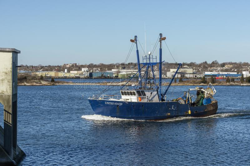 Commercial fishing boat United States approaching New Bedford hurricane barrier. New Bedford, Massachusetts, USA - February 6, 2019: Commercial fishing vessel stock photography