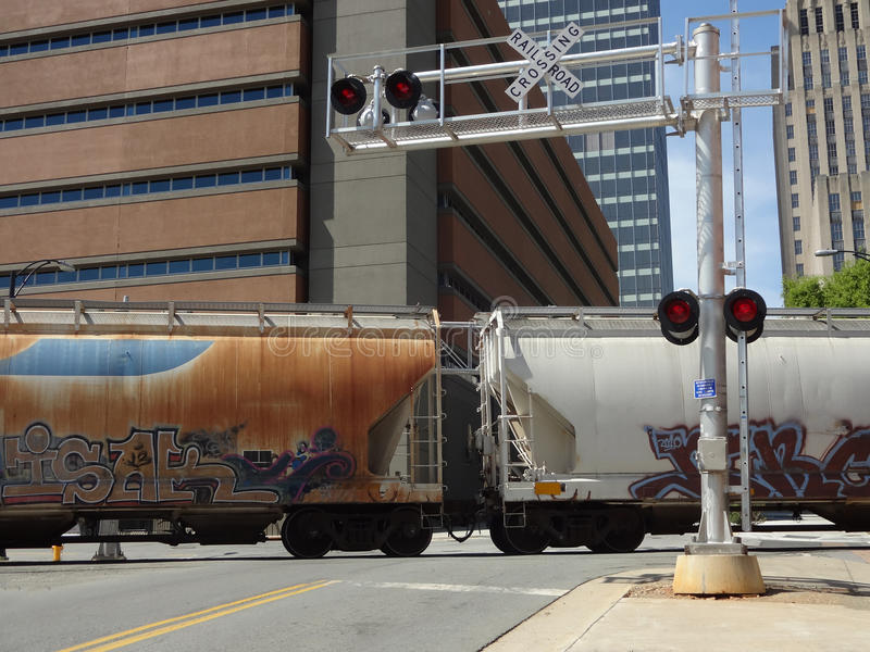 Commercial Freight Train Crosses Over Road at a Railroad Crossing royalty free stock photography