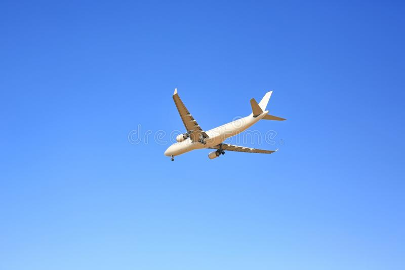 Commercial jet airplane flight on blue sky background. Seen from below.  stock image