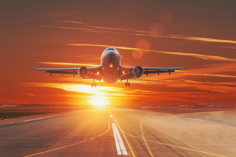 Commercial jet airplane flying over runway dramatic sunset sky.  royalty free stock photography