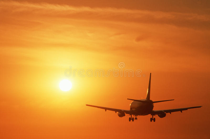 Commercial jet flying into sunset royalty free stock image