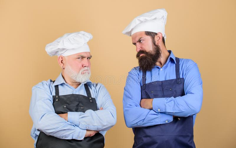Commercial kitchen at restaurant. professional chefs. men in cook hat. mature bearded chef. tired of cooking. masters of. Kitchen. who is the best. fami dinner stock photography
