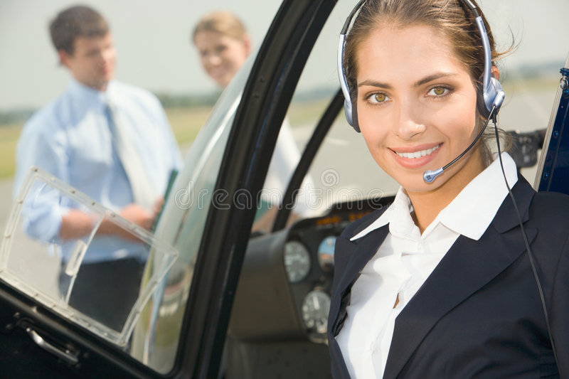Commercial pilot. Confident pilot with headset smiling in the private helicopter