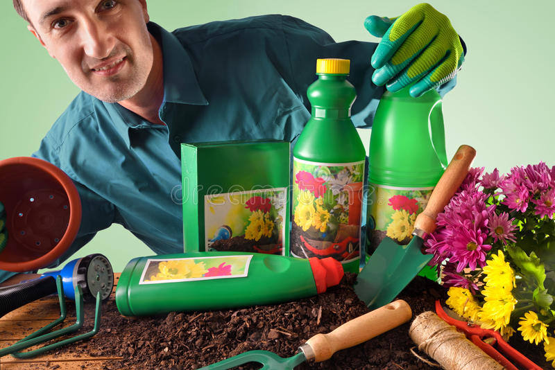 Commercial showing bottles and containers of gardening products. Worker with bottles and containers of gardening products for the growth of plants. With flowers stock image