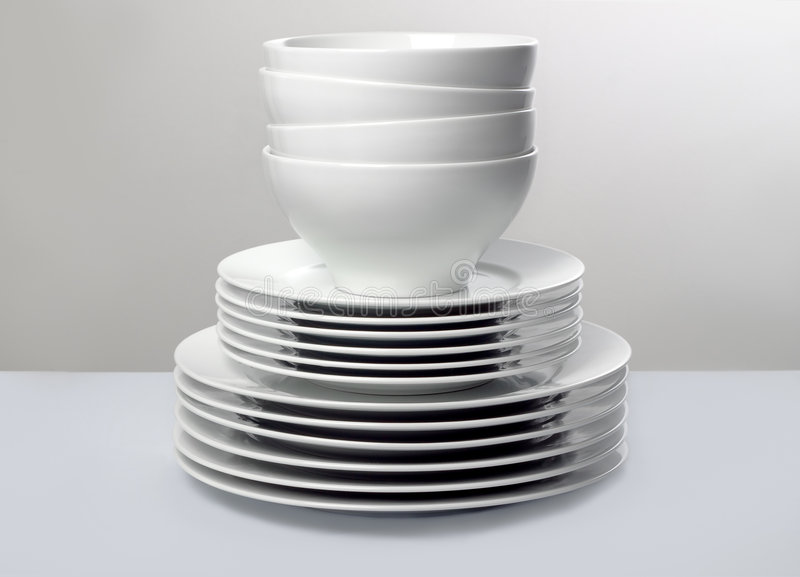 Commercial white dishes on neutral background stock photography