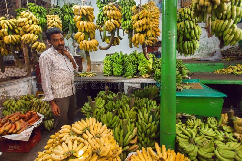Commerciante della banana che vende frutti verdi e gialli sul mercato degli agricoltori fotografia stock