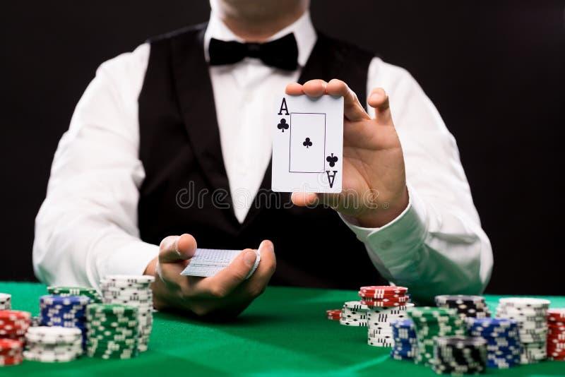 Commerciante di Holdem con le carte da gioco ed i chip del casinò fotografie stock