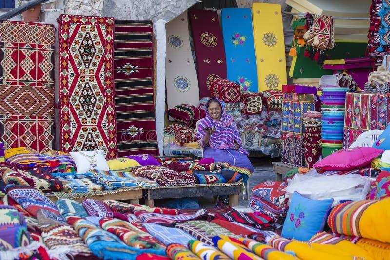 Commerciante femminile al mercato di Souq Waqif in Doha, con i tappeti multicolori, i kilims ed altri oggetti Doha, Qatar fotografia stock libera da diritti