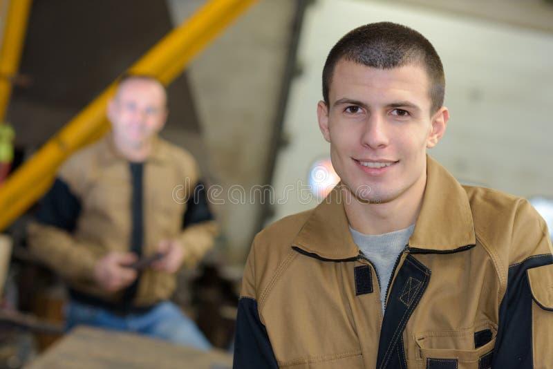 Commerciante sorridente del ritratto giovane in uniforme fotografie stock