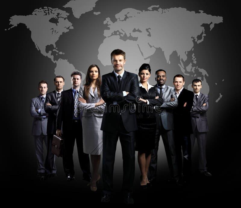 Commercieel die team van jonge zakenlieden wordt gevormd die zich over een donkere achtergrond bevinden stock afbeeldingen