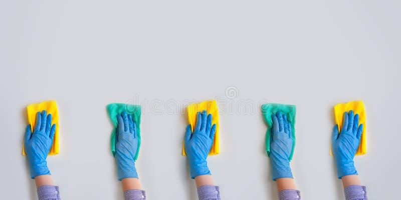 Commercieel schoonmakend bedrijf De werknemer dient blauwe rubber beschermende handschoen in Algemene of regelmatige schoonmaakbe stock afbeelding