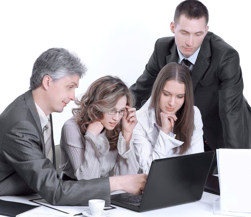 Commercieel team die bedrijfskwesties bespreken die achter een Bureau zitten stock fotografie