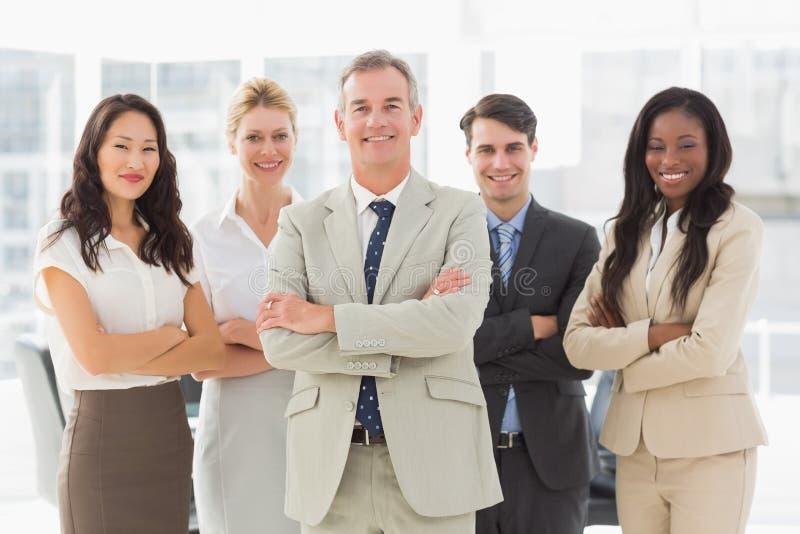 Commercieel team die bij camera met gevouwen wapens glimlachen royalty-vrije stock afbeelding