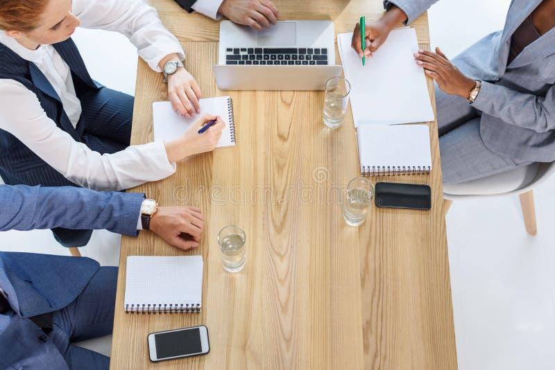 Commercieel team die in blocnotes tijdens vergadering schrijven royalty-vrije stock fotografie