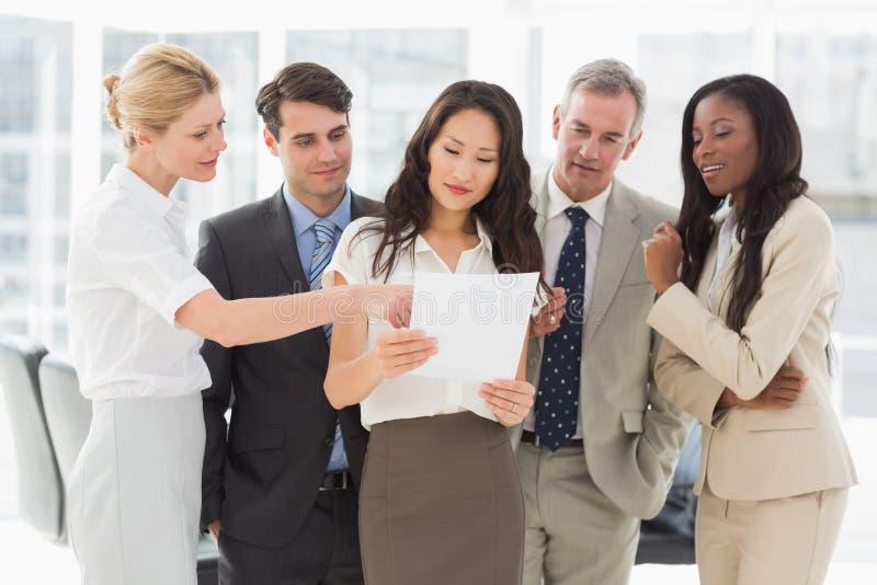 Commercieel team die document samen bekijken stock afbeelding