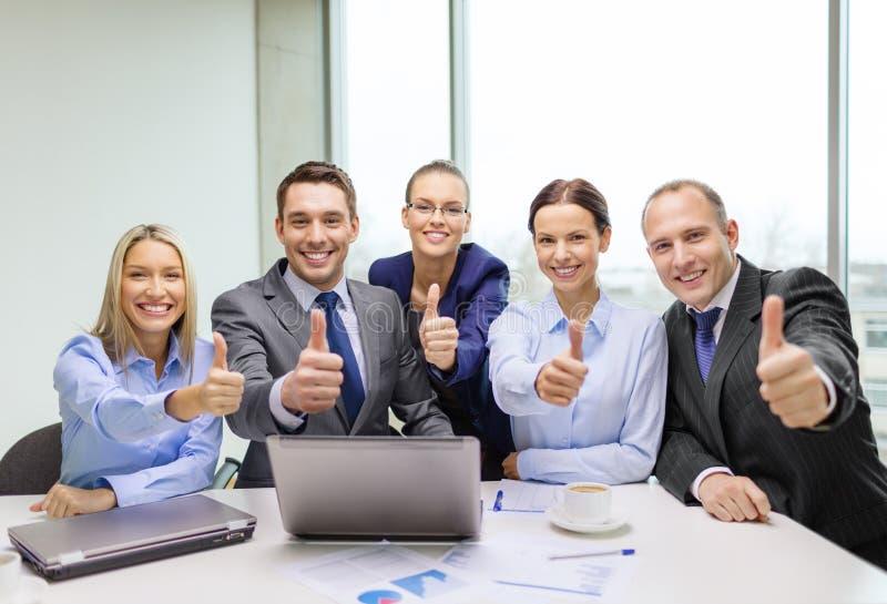 Commercieel team die duimen in bureau tonen royalty-vrije stock afbeelding