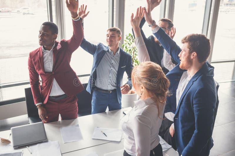 Commercieel team die een hoog fivesgebaar geven aangezien zij lachen en hun succes toejuichen stock afbeeldingen