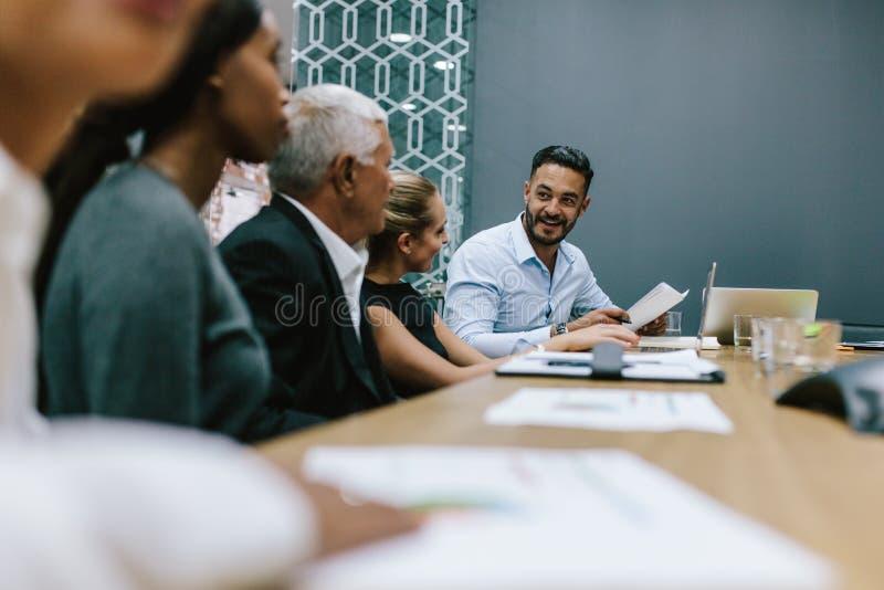 Commercieel team die een vergadering in bureau hebben stock afbeeldingen
