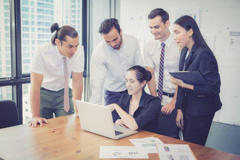 Commercieel team die een vergadering hebben die laptop met behulp van tijdens een vergadering royalty-vrije stock afbeelding