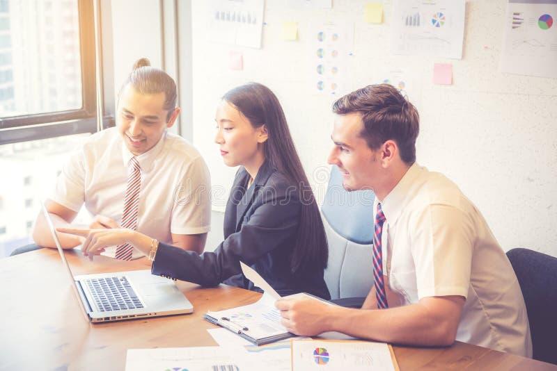 Commercieel team die een vergadering hebben die laptop met behulp van tijdens een vergadering en een heden stock afbeeldingen