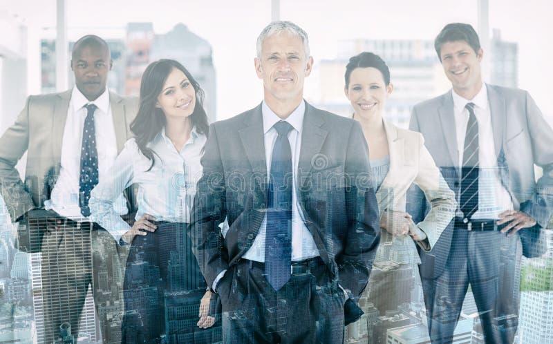Commercieel team die en zich rechtop met hun handen op hun heupen glimlachen bevinden stock foto
