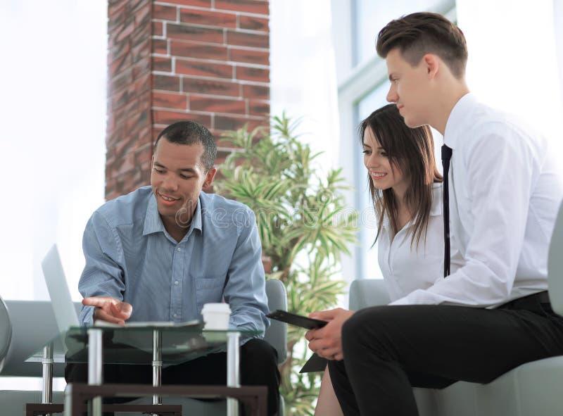 Commercieel team die laptop het scherm bekijken, die achter een Bureau zitten stock fotografie